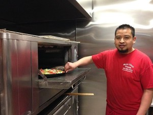 Antonio Moran puts a tomato, broccoli and red pepper pizza in the oven. More Than Pizza new haven