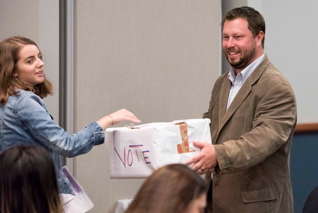 A high school student submits her ballot during High School Journalism Day, while speaker Paul Singley looks on. | Vern Williams photo.